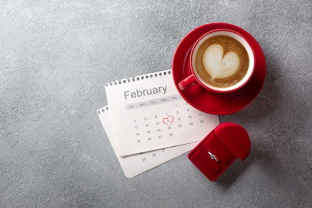 Valentine's day greeting card. red coffee cup, ring and gift box over february calendar. Premium Photo