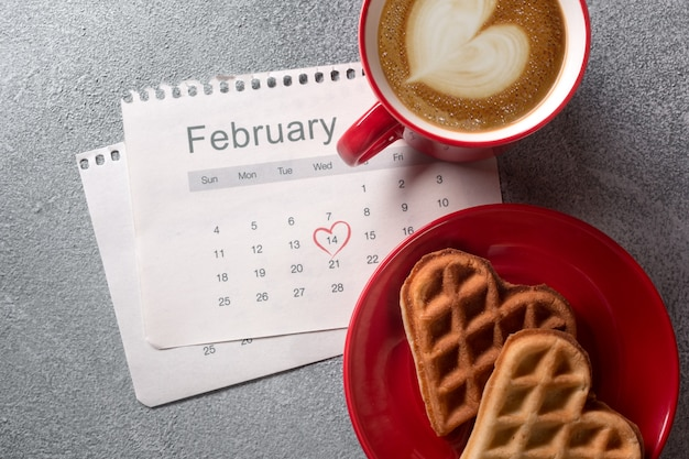 Valentine's day greeting card with coffee cup and heart shaped cookies on grey background. Premium Photo