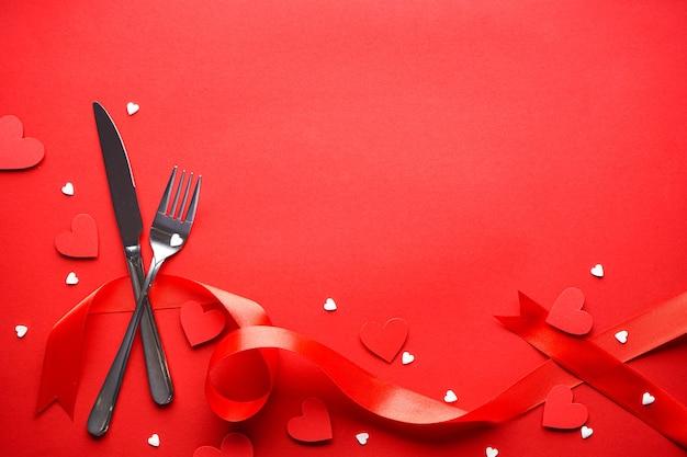 День святого валентина. концепция любви. день матери. сердечки со столовыми приборами и красной лентой на красном фоне, с пространством для текста, плоская планировка. Premium Фотографии
