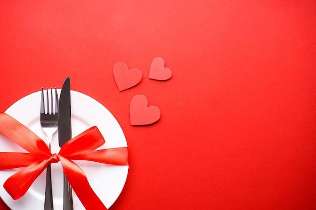 День святого валентина. концепция любви. день матери. сердечки со столовыми приборами на белой тарелке с красной лентой на красном фоне, плоская планировка, с пространством для текста. Premium Фотографии