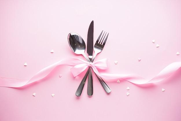 День святого валентина. день матери фон. концепция любви. сладкие сердца и столовые приборы на белой тарелке с розовой лентой на розовом фоне, плоская планировка. Premium Фотографии