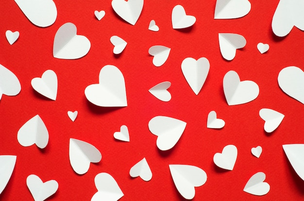 Valentine's day romantic background. white paper hearts at red backdrop, top view. Premium Photo