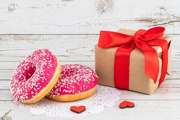 День святого валентина романтический завтрак. подарок, сердечки и пончики. день святого валентина концепция копировать пространство Premium Фотографии