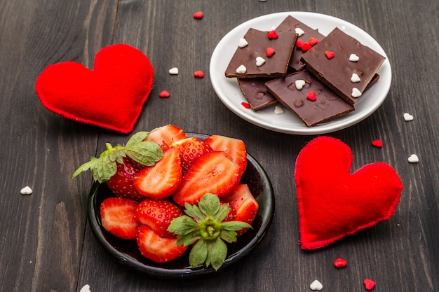Valentine's day romantic concept. chocolate, fresh ripe strawberry, red felt hearts. sweet dessert for lovers. Premium Photo
