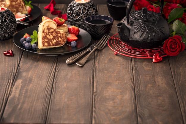 ハート、緑茶、黒のティーポット、キャンドル、バラの形のおいしいパンケーキでバレンタインデーの表面。バレンタインデーのコンセプトグリーティングカード。コピースペース Premium写真