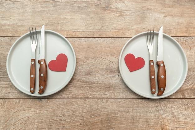 Сервировка табла ко дню святого валентина с тарелками и столовым серебром на деревенском деревянном фоне концепция романтического ужина и свиданий Premium Фотографии