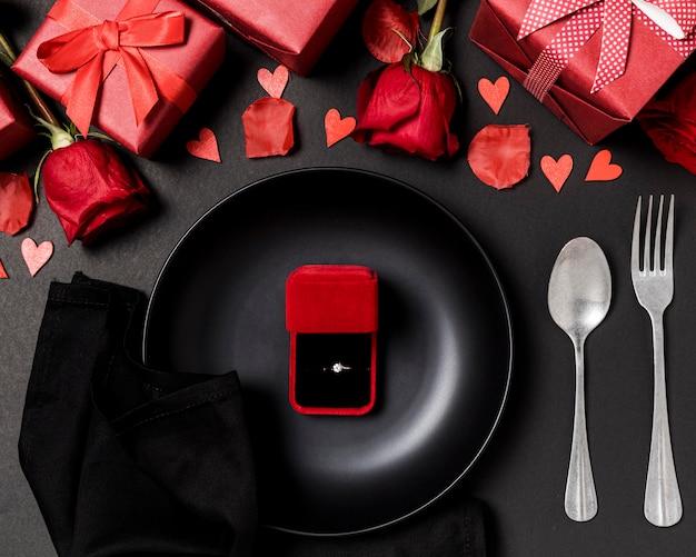 Set da tavola di san valentino con anello di fidanzamento su piatto e rose Foto Gratuite