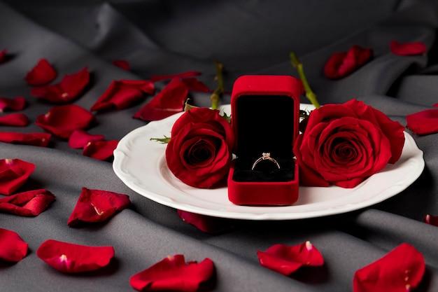 バラと婚約指輪をプレートにセットしたバレンタインデーのテーブル 無料写真