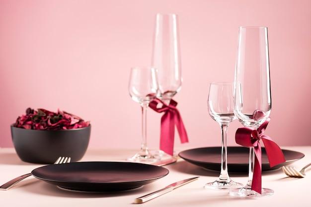 Сервировка стола ко дню святого валентина на двоих с засушенными цветами на розовом фоне Premium Фотографии