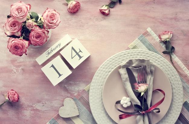 Установка таблицы дня валентинки, взгляд сверху на свете - розовой стене. деревянный календарь, салфетка и посуда, украшенные бутонами роз и лентами, керамическими цветами и розовыми розами. Premium Фотографии