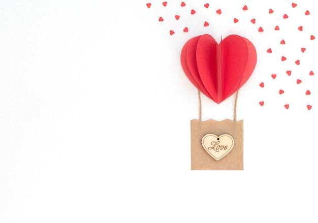 その上に木製のハートとバスケットと赤いハートの風船とバレンタインデーの白い背景 Premium写真