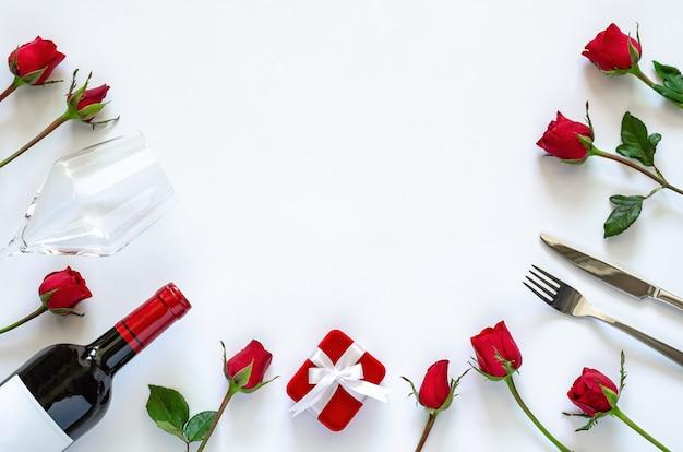 Обеденный набор валентина на белом фоне с красными розами. Premium Фотографии