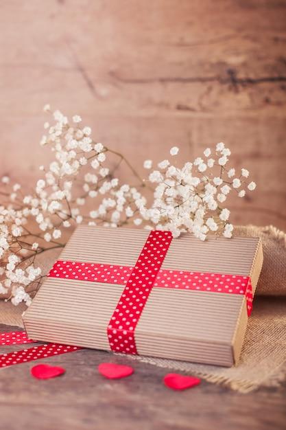 Regalo di san valentino con nastro rosso su legno Foto Gratuite
