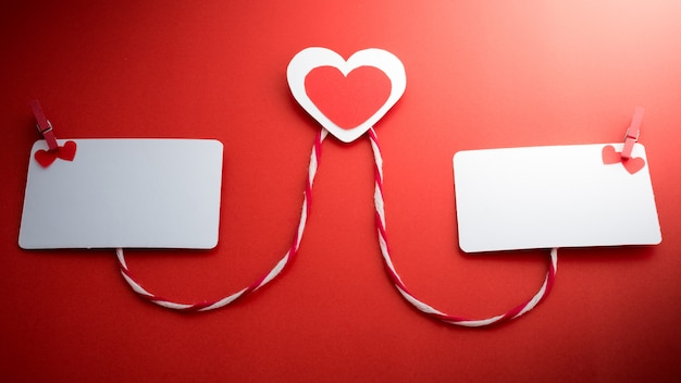 Valentine's paper hearts with a blank business card and clothespin on a red background Premium Photo