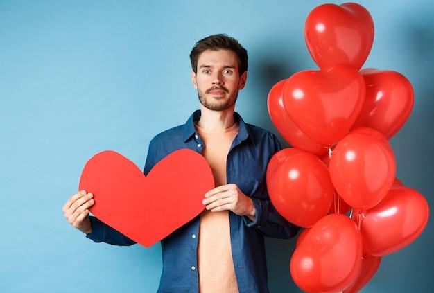 발렌타인 데이 및 사랑 개념. 빨간 종이 심장 컷 아웃을 표시 하 고 낭만적 인 풍선 근처에 서, 연인을보고, 파란색 배경 위에 서있는 젊은 남자. 프리미엄 사진