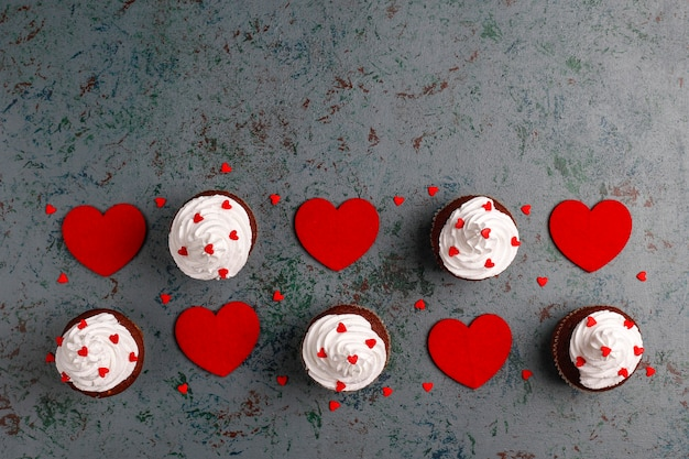 Valentines day background, chocolate cupcakes with heart shaped candies,top view Free Photo