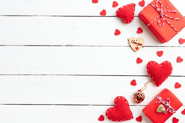Valentines day background, red gift box with red heart on wooden background. Premium Photo