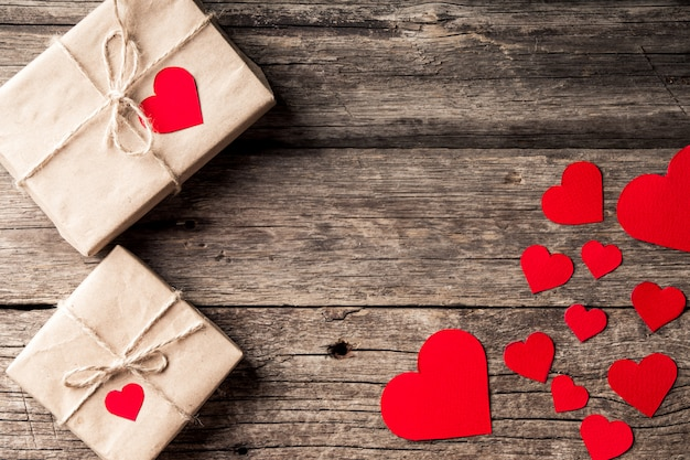 День святого валентина фон. красные сердца, ленты и подарочные коробки на деревянных фоне. Premium Фотографии