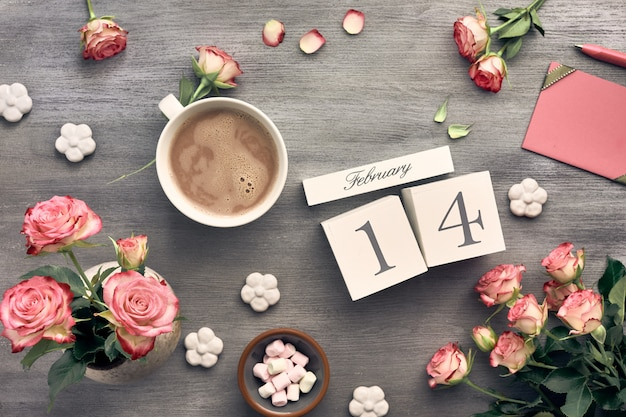Valentines day background with pink roses, wooden calendar, greeting card and decorations Premium Photo
