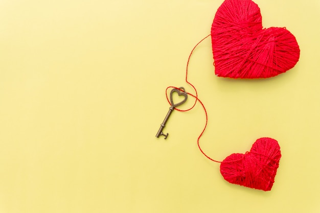 Valentines day card with red hearts and key on yellow background. Premium Photo