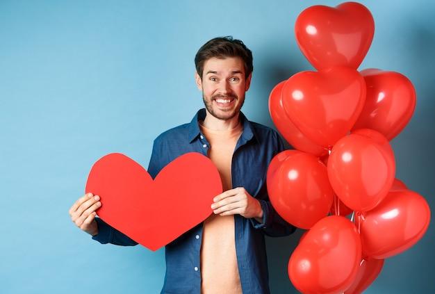 발렌타인 데이 개념. 웃는 남자는 내가 당신을 사랑한다고 말하고, 종이 붉은 심장 컷 아웃을 들고, 낭만적 인 풍선, 파란색 배경 근처에 서 있습니다. 프리미엄 사진