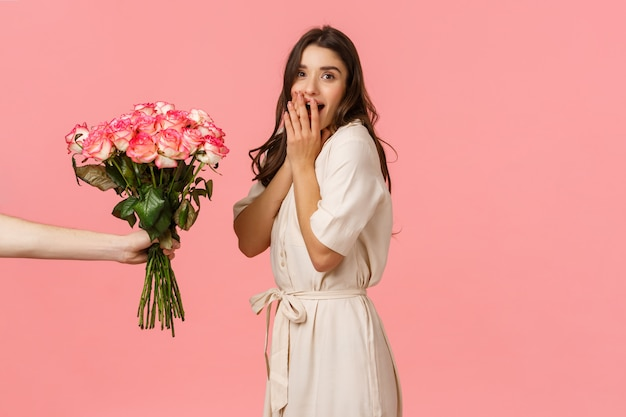 Valentines day, delivery and beauty concept. amazed woman gasping and looking  surprised as someone giving her beautiful bouquet flowers, congratulations with anniversary, pink wall Premium Photo