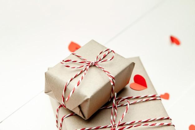 Подарочная коробка на день святого валентина и красные бумажные сердца на белом деревянном столе Premium Фотографии