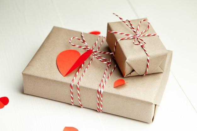 Подарочная коробка на день святого валентина и красные бумажные сердца на белом Premium Фотографии