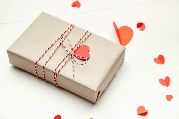 Подарочная коробка на день святого валентина, украшенная красными сердечками на белом деревянном столе Premium Фотографии