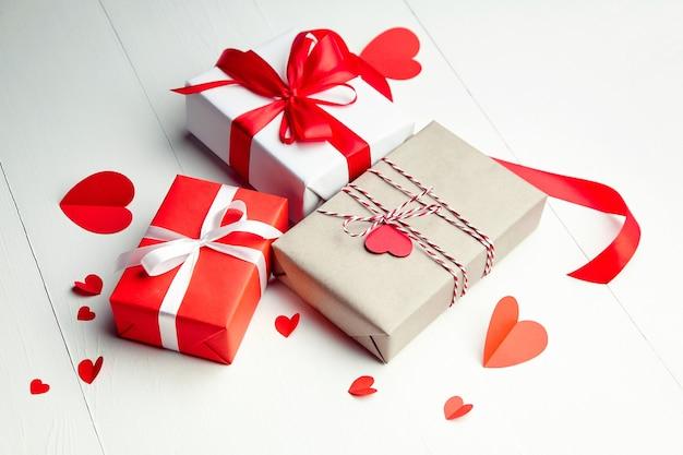 Подарочные коробки на день святого валентина и красные бумажные сердца на белом деревянном столе Premium Фотографии