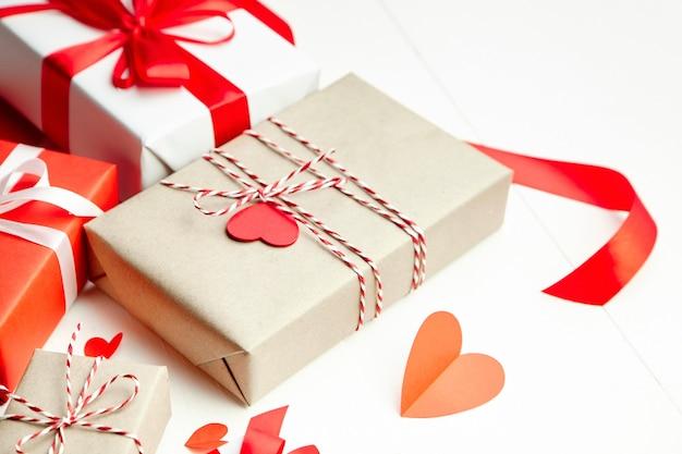 Подарочные коробки на день святого валентина, украшенные сердечками на белом деревянном столе Premium Фотографии