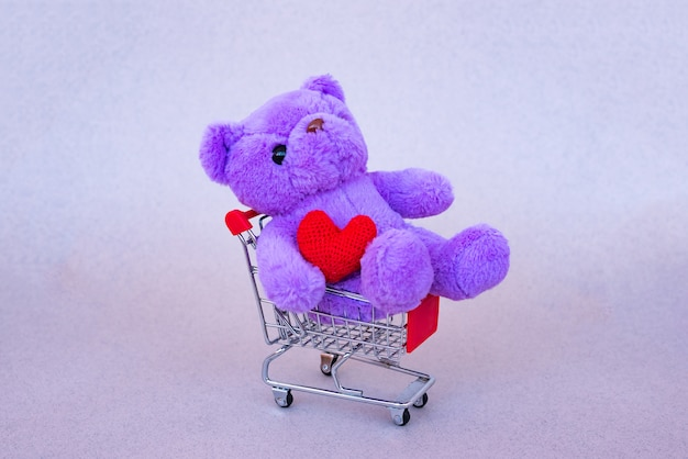 Valentines day gift. lilac teddy bear, bright plush toy with red heart in supermarket trolley. retro romantic style. Premium Photo