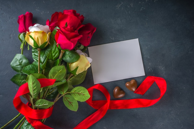 Valentines day greeting card concept with red rose flowers, champagne, chocolates and gift box Premium Photo
