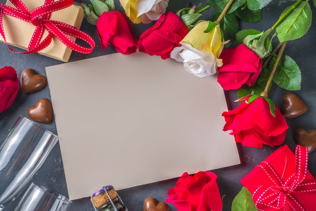 Valentines day greeting card concept with red rose flowers, champagne, chocolates and gift box. Premium Photo