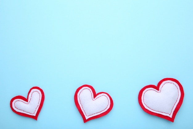 Valentines day greeting card. handmaded hearts on blue background. Premium Photo