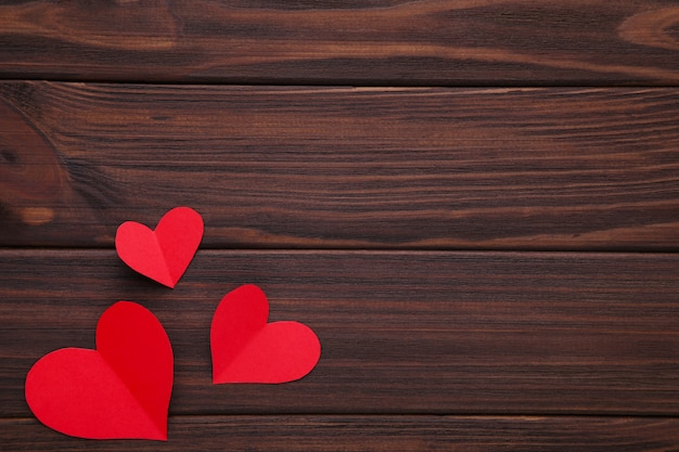 Valentines day greeting card. handmaded red hearts on brown background. Premium Photo