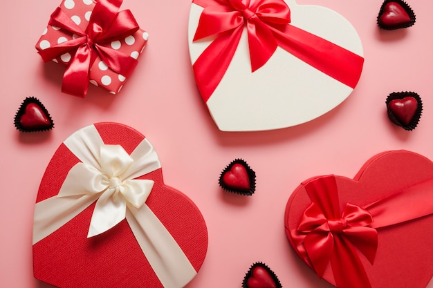 Valentines day greeting card. pattern of red gift boxes heart shaped and chocolate sweets on pink. view from above. Premium Photo