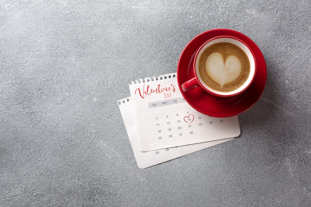 Valentines day greeting card. red coffee cup over february calendar. top view Premium Photo