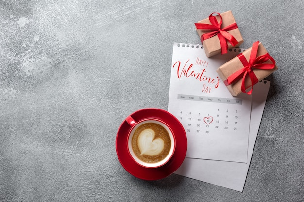 Valentines day greeting card. red coffee cup and gift box over february calendar. top view Premium Photo