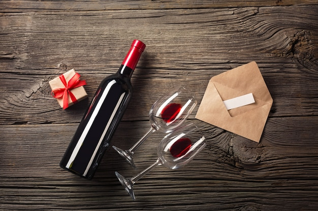 Valentines day greeting card. red wine, gift box and glasses on wooden table Premium Photo