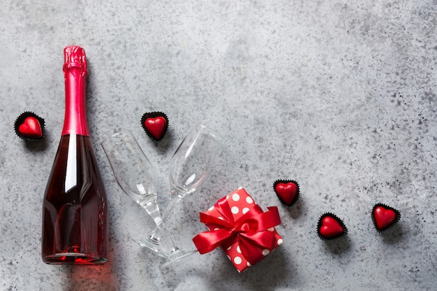 Valentines day greeting card with bottle of sparkling wine, gift box, heart shaped candies on grey. romantic dating concept. view from above. Premium Photo