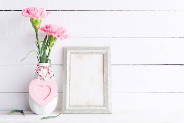 Valentines day, love concept. pink carnation flower in vase with old vintage picture frame Premium Photo