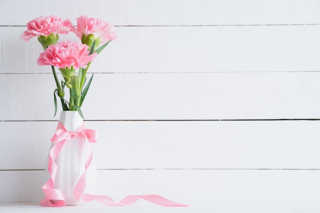 Valentines day and love concept. pink carnation in vase on wooden background. Premium Photo