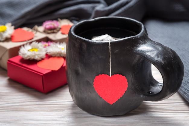バレンタインデーの朝、木製の机の上のティーカップ Premium写真
