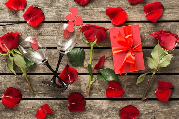 День матери день святого валентина красная подарочная коробка с цветами лепестками роз бумажные сердечки и бокалы на деревянном столе Premium Фотографии