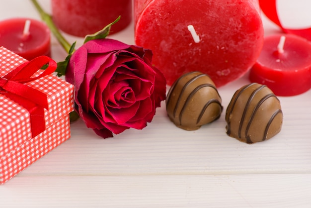 Valentines day red background with red roses and chocolate on a white wooden table. Premium Photo