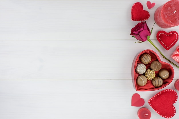 Valentines day romantic decoration with roses and chocolate on a white wooden table. Premium Photo