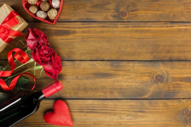 バラ、ワイン、チョコレート、茶色の木製テーブルの上のバレンタインの日ロマンチックな装飾 Premium写真
