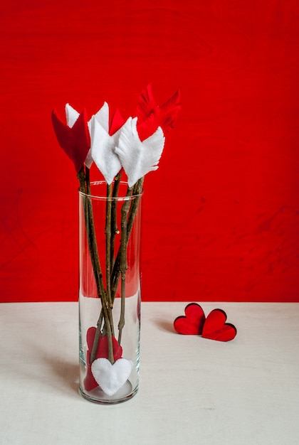 Valentines day twig arrows and hearts on red wooden background and glass vase. Premium Photo