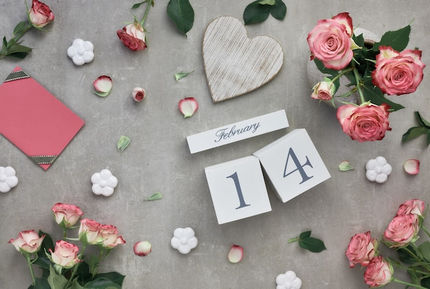 Valentines day with pink roses and wooden calendar Premium Photo